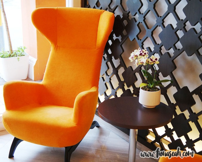 Comfy orange guest chairs near the entrance