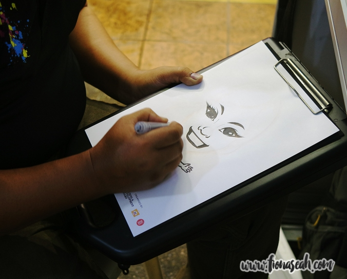Caricature artist drawing a portrait of me with so much skill