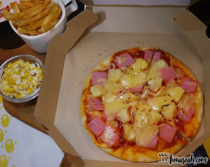 Mel and Minions are hungry! They want pizza! Unexpectedly, a live singing competition awaits them... Hawaiian pizza topped with chicken ham and pineapple, with corn and French fries on the side.