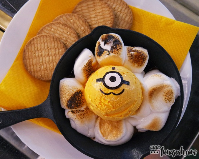 Perfectly browned marshmallows surround a lone Minion (made of mango ice); sandwich molten marshmallow with biscuits for a campfire s'more effect!